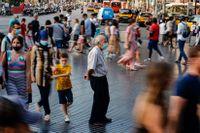 En man bär ansiktsmask i Kataloniens huvudstad Barcelona. Efter fler smittofall har regionen skärpt restriktionerna.
