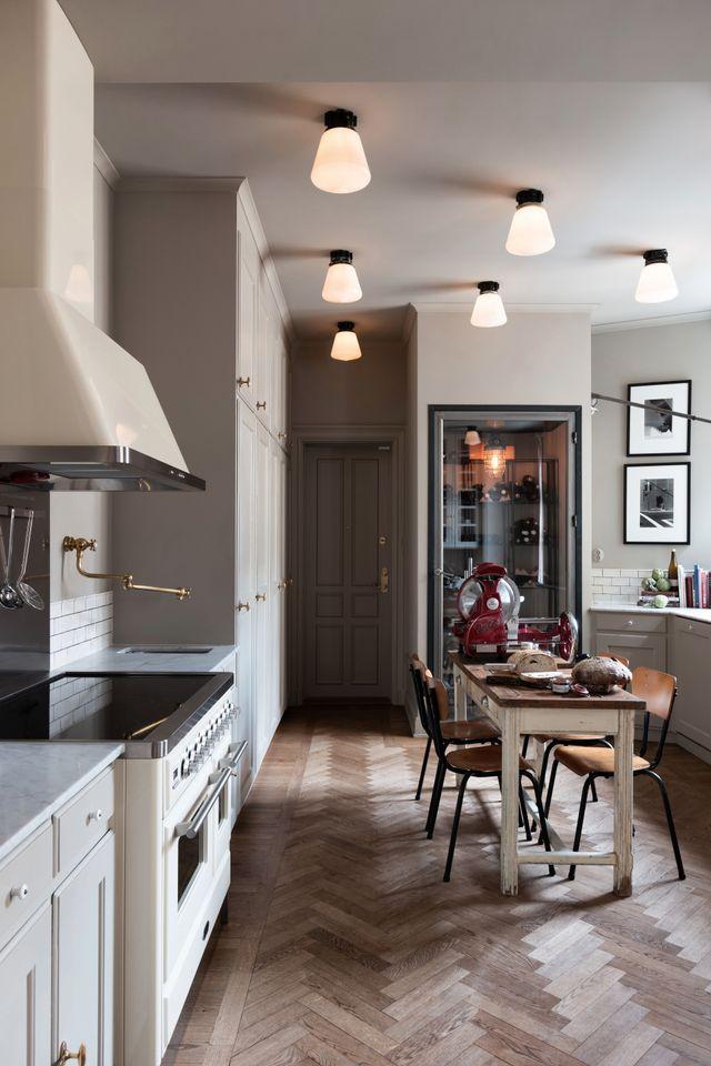 I köket är både tak, väggar och eluttag målade i samma  nyans. Spisen kommer från Ilve och de svenska 20-talslamporna i taket är köpta i en antikvitetsbutik.