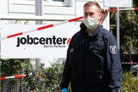 En polis med munskydd utanför arbetsförmedlingen i Berlin där en kvinna insjuknade.