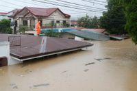 En man står på taket till sitt hem i Marikina i Filippinerna efter att tyfonen Vamco orsakat översvämningar.
