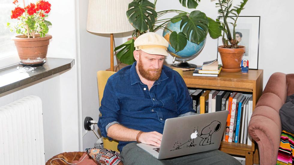 Fotografen Daniel Nilsson i en av sina egna hemmakontorsplatser. Fåtöljen i vardagsrummet.