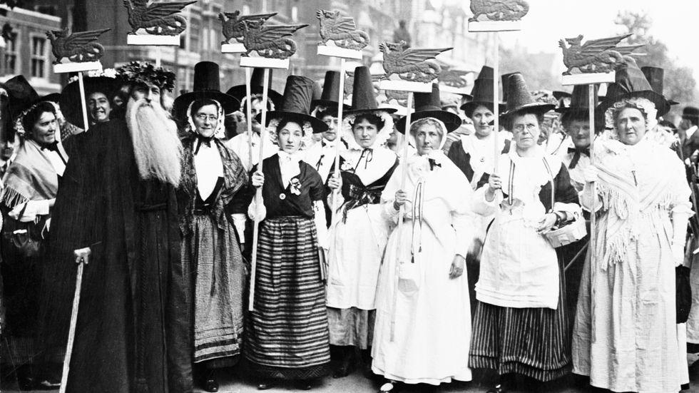 Walesiska suffragetter i folkdräkter bär på drakbilder hämtade från den walesiska nationsflaggan, Y Ddraig Goch, 1911.