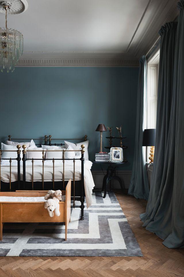Det är lugna, mörka toner som gäller i lägenhetens före detta cigarrum, i dag parets sovrum. Den franska gjutjärnssängen är ett auktionsfynd från 1910-talet.