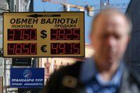 En man går förbi ett växlingskontor i Moskva under onsdagen. Den ryska rubeln har tappat i värde den senaste tiden.