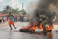 En soldat försöker släcka ett brinnande däck under oroligheterna i Brundis huvudstad Bujumbura.