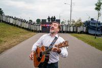 En man spelar gitarr framför kravallpolis i Belarus.