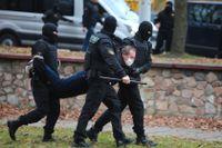 En man bärs iväg i armar och ben vid en demonstration i Minsk, den 1 november i fjol. Arkivbild.