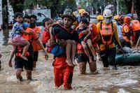 Räddningsarbetare bär bort barn från en översvämmad gata i staden Marikina, öster om Filippinernas huvudstad Manila.