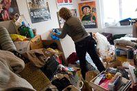 """Gunnel i sitt """"adhd-rum"""" där högar med kläder, kartonger, julpynt och annan bråte klättrar upp mot taket."""