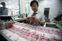 En bankkassör räknar sedlar i staden Huaibei i östra Kina.