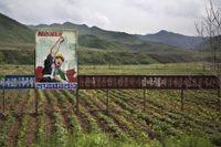 En propagandaaffisch vid ett fält i Samsu, Nordkorea.