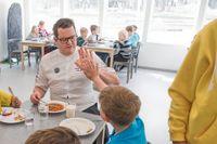 Kocklandslagskocken Fredrik Andersson äter med barn på Byleskolan i Täby.