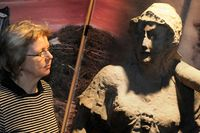 """Utställningskommissarien Lena Hejll med sandstenskulpturen """"Tapperheten"""" som har suttit på en sandstenskyrka i Kristianstad."""