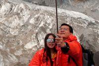 Ett turistpar tar en selfie framför Baishui-glaciären i Kina – en av de snabbast smältande glaciärerna i världen. Vi behöver ägna oss åt en underkastelse som – till skillnad från den som Greta Thurfjell skrivit om – sätter det personliga begäret åt sidan. Annars gör vi på sikt vår planet obeboelig.