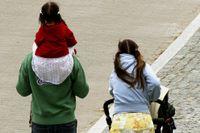 Barnfamilj med barn och barnvagn.