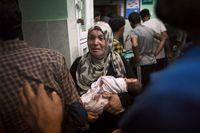 En skadad bebis kommer in till sjukhuset i Gaza efter att Israel bombat en FN-skola.