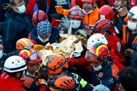 Räddningsarbetare bär en treårig flicka som grävts fram vid liv ur rasmassorna 65 timmar efter det dödliga skalvet.