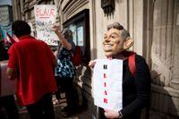 En demonstrant med en Tony Blair-mask kallar Storbritanniens förre premiärminister en lögnare på onsdagen när rapporten om Irak släpptes.