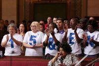 Supportrar av höjd minimilön applåderar.