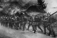Augusti 1914. Soldater i det tyska infanteriet marscherar genom en brinnande by i Belgien.