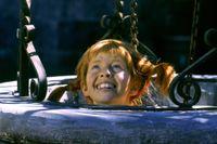 Barnskådespelaren Inger Nilsson i rollen som Pippi Långstrump gömmer sig i en brunn under filminspelningen av 'Pippi på de sju haven' på borggården i Vaxholms fästning strax utanför Stockholm i augusti 1969.