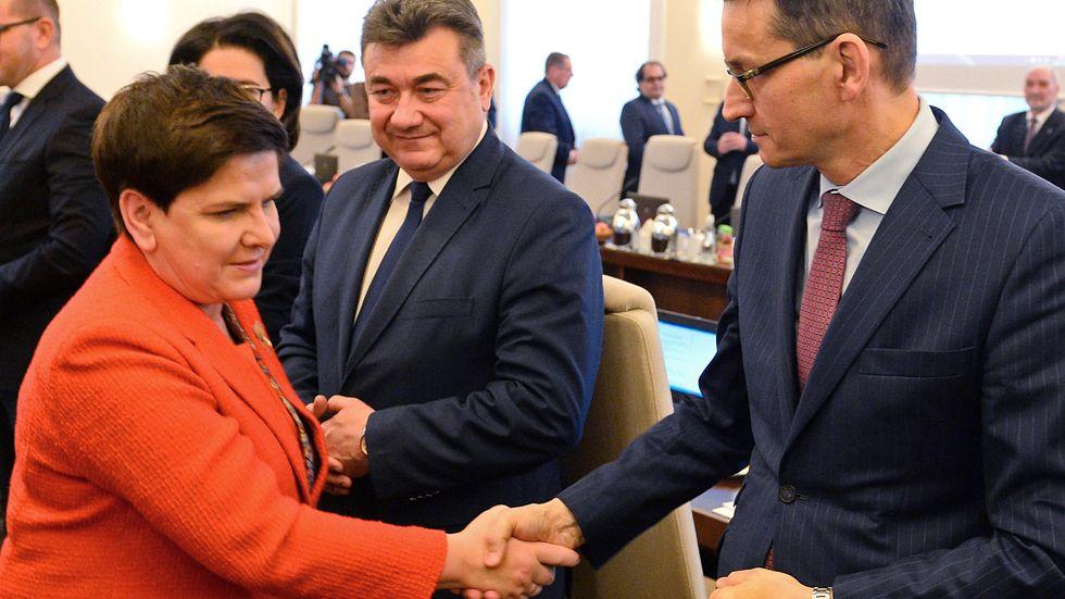 Polens premiärminister Beata Szydlo ersätts av finansminister Mateusz Morawiecki. Här skakar de hand på ett regeringsmöte tidigare i veckan.