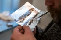 En man röker heroin i ett inhaleringsrum på en vårdinrättning i Oslo.