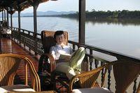 Eftermiddag ombord på fartyget byggt av jakaranda som långsamt tar sig nedströms på Mekong mot gränsen mellan Laos och Kambodja. Ett soltak av tyg är uppspänt i fören och silar det starka ljuset. Floden som en grön matta och det är tyst och det är stilla.