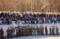 Berlinbor har samlats ovanpå den mur som redan har börjat raseras i november 1989. Östtyska soldater tittar på.
