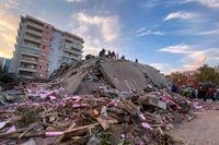 Räddningsarbetare letar efter överlevande i rasmassorna efter en byggnad som kollapsade i staden Izmir i Turkiet.