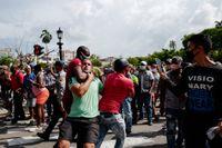En demonstrant mot den kubanska regeringen släpas bort av polis.