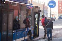 En blå SL-buss i centrala Stockholm tar upp passagerare vid en hållplats.
