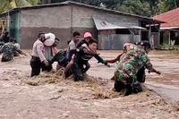 Soldater och poliser hjälper invånarna att komma över en flod i Indonesien.