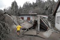 Invånare vid ett hus som förstörts av vulkanaska i södra Filippinerna.
