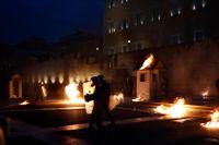 Våldsamma demonstranter kastar bensinbomber mot poliser utanför parlamentet i Aten.