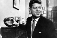 JohnF Kennedy visar upp en halv kokosnöt, monterad som prydnadsföremål. När Kennedys torpedbåt rammades under andra världskriget, ristade han ett meddelande till andra USA-styrkor i nöten.