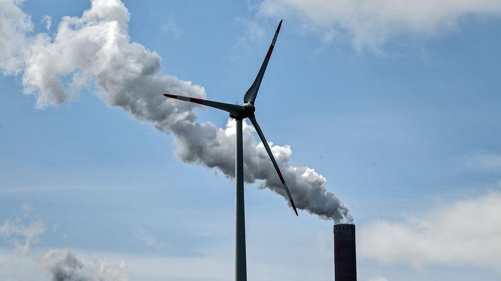 Hur måste energiproduktionen ställas om? Bild på en vindturbin och en kolkraftsskorsten i Gelsenkirchen tidigare i vår.