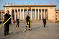 Säkerhetsvakter flyttar en avspärrning framför Folkets stora hall i Peking där nationella folkkongressen öppnar på söndag.