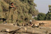 De israeliska armeförbanden nära Gaza förstärktes på fredagen och var beredda att gå in över gränsen så snart regering gav order.