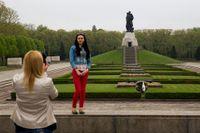 Rysktalande turister i Berlin tar foton vid Sovjetunionens monument över erövringen av Berlin 1945.
