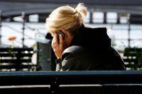 En kvinna sitter på en parkbänk och pratar i en mobiltelefon.