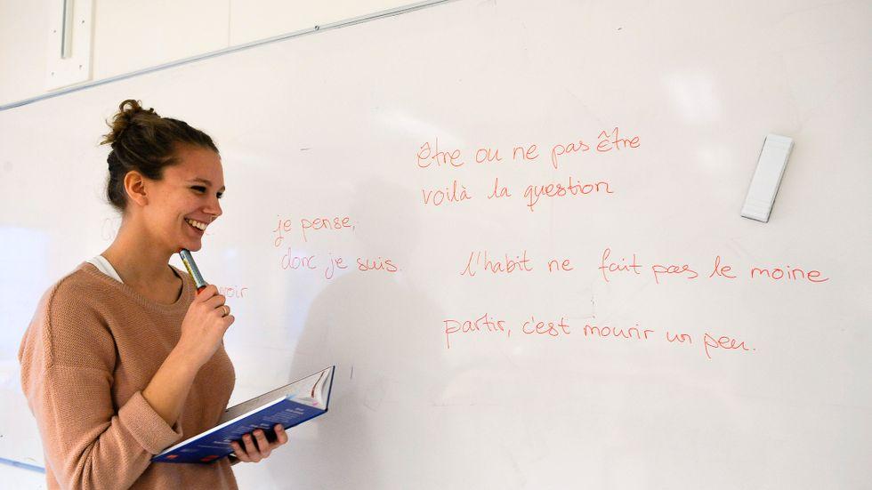 En kvinnlig student skriver på franska på vita tavlan på Stockholms universitet.