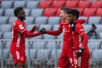 Alphonso Davies, till vänster och Kingsley Coman, till höger, gratulerar Robert Lewandowski till hans rekordmål mot Freiburg.