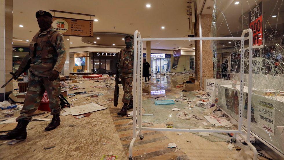 Soldater patrullerar i ett förstört köpcentrum i Soweto.