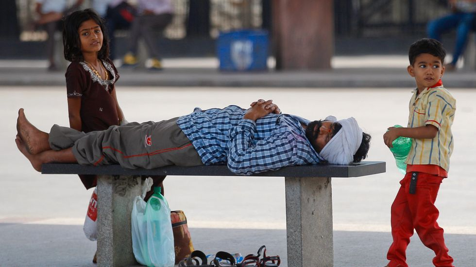 Barn leker vid en sovande man  på en övergiven busshållplats under en storstrejk i Bangalore, Indien.