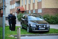 En polis talar med en kvinna utanför det hus i Gottsunda i Uppsala, där en man hittades skjuten.