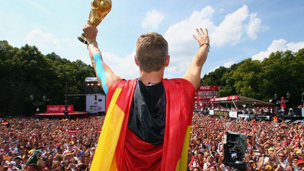 Bastian Schweinsteiger hyllas med pokalen vid Brandenburger Tor.