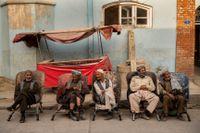 Män sitter längs vägen i Kabul och väntar på att få jobb.