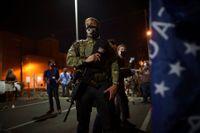 En beväpnad Trump-supporter utanför röstkontoret i Maricopa County, Phoenix.