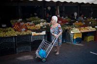En äldre kvinna handlar frukt och grönsaker i Aten. Många grekiska pensionärer är missnöjda med de åtstramningar som har genomförts under åren av stödprogram. Arkivbild.